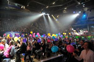 Publiken med ballonger under strålkastarljus i Tegera Arena i Leksand under deltävling tre i kvalet till Melodifestivalen 2012. Arkivbild. Foto: Jessica Gow/TT