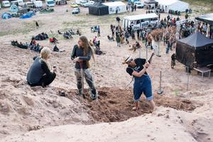 Vidar Svensson och Niklas Hammarström gräver fram en sandskulptur bakom scenen.
