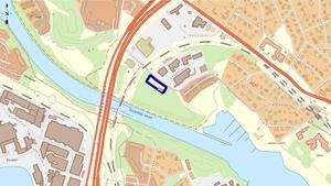 Den inramade blå rektangeln visar var det nya flerbostadshuset ska ligga. Den streckade linjen visar pendeltågsspåret och de tjocka röda strecken utgör motorvägen.