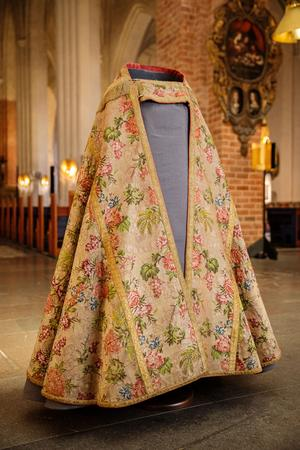 Kåpan går under namnet Biskopskåpan Adolf Fredrik eller Kröningskåpan. När drottning Lovisa Ulrika och kung Adolf Fredrik skulle krönas beställdes 14 korkåpor från kostymskräddare i Paris till Sveriges biskopar. Stiften fick själva bekosta sina respektive kåpor. Västeråskåpan är utseendemässigt lika som Linköpings, Skaras och Strängnäs kåpor. Kåpan är utförd i blommig sidenbrokad som är vävd i Lyon och kantas av ett brett guldband runt hela kåpan, samt guldfransar på ryggskölden. Fodret är i rosa siden (troligen ej ursprungligt).  Foto: Henrik Mill/Svenska kyrkan Västerås