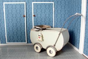 Blåmönstrad tapet och barnvagnen som Carina legat i.