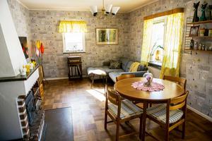 Vardagsrummet går i grått, svart och gult och rymmer både soffhörna och matbord.