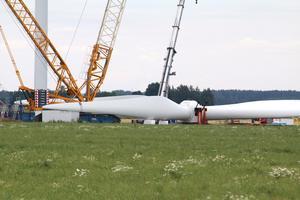 Rotorn som lagts ner för att byta lager till en vinge väger 65 ton. Här syns också den stora kranen med motvikter vid ett av vindkraftverken vid Mosås.