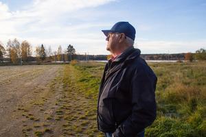 Tommy Larnhed tittar ut över grusplanen som blivit sönderkörd av en traktor. Enligt honom har han påtalat detta till kommunen, men inga åtgärder har skett på grushögarna som bildats.