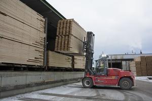 Truckföraren Magnus Westman ställer in två virkespaket på vardera fem-sex ton i den stora torkanläggningen. När det sågade virket kommer ut på andra sidan är det klart att köras till Domsjö.