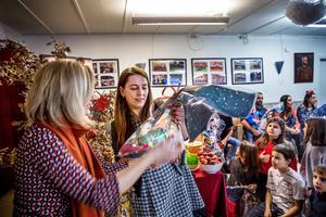 Aktivitetsledaren Marina Zubic delar ut julklappar till barnen.