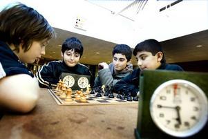 KONCENTRATION. Joakim Skoglund och Vinyar Shallal möts i ett parti schack efter att turneringen är över. Kompisarna Blend Wrya och Rezhin Kader, som också varit med och tävlat, ser på.