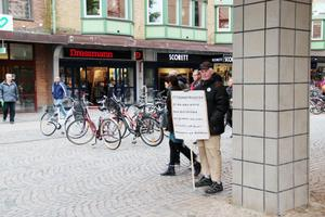 Olle Ljungbeck brukar stå utanför Nian med skyltar som har olika budskap.