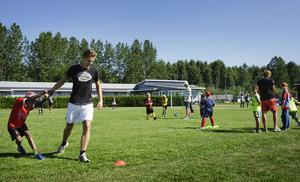 Det är uppenbart att ledarna och deltagarna i fotbollsskolan har roligt ihop.