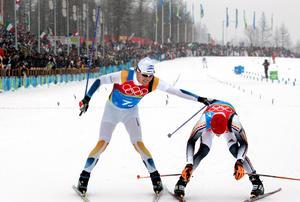 Mathias Fredriksson jublar när han åker in över mållinjen och säkrar ytterligare en bronsmedalj till Sverige. Till höger ses silvermedaljören Tobias Angerer från Tyskland. Bild: Pontus Lundahl/TT.