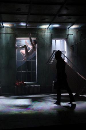 Gregor Samsa, huvudperson i Kafkas Förvandlingen, klättrar på väggarna som den insekt han har förvandlats till. Gregor spelas av Patrick Henriksen. Här skymtar också Anna Stenbergs stumma svarta atmosfärskapande figur.Foto: Yoshi Omori