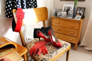 Röda handskar och klackskor och inramade foton på byrån.