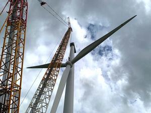 Rotorn med hubben och de tre vingarna väger 65 ton och de lyfts ner från 100 meters höjd av en kran som väger 610 ton.  Från vingspetsarna hänger rep ner till marken där det står folk och håller emot.Foto: Erik Josefsson