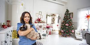 Maria Rönnerfjäll med katten Ninni i sitt ljusa hem med den drygt  tre meter höga granen. Maria och dottern börjar pynta tidigt. Det gör henne harmonisk att skapa julstämning,  säger hon. Foto: Lennye Osbeck
