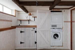Tvättstugan finns i källarplanet och både tvättmaskinen och torktumlaren döljs bakom dörrar i gammaldags stil.Foto: Svensk fastighetsförmedling.