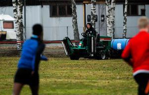 Rasmus Karlsson vårdar gräset samtidigt som laget tränar.