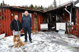 Petra Jacobsson och Peter Keränen – tillsammans med lapphunden Pepsi, som sannolikt räddade deras och deras fyra barns liv – framför det totalförstörda huset.