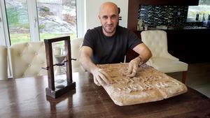 Kamil Yacoub formar kilskrift i sin lertavla.