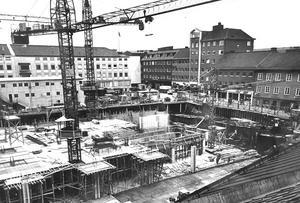8 september 1965. Det nya varuhusbygget i Västerås centrum mellan Torggatan och Köpmangatan skjuter allt mer i höjden och det fula såret i stadsbilden börjar läkas. Planet som syns på bilden kommer att rymma livsmedelsmarknaden - den största i Sverige sägs det - och i källarvåningarna som syns därunder kommer lagerutrymmena att bli belägna. När huset står invigningsklart i september 1966 kommer det att resa sig i höjden med sex våningar, men ännu har man inte kommit över markytan.