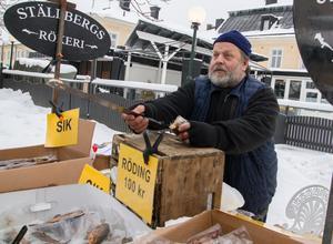 Dennis Fält Ström har fullt upp med att erbjuda smakbitar av rökt fisk och svara på frågor som var fisken kommer ifrån.