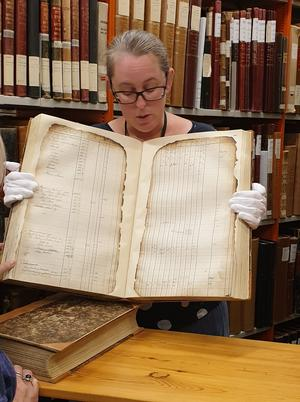 Mona Bergman visar en av många kyrkböcker som restaurerats