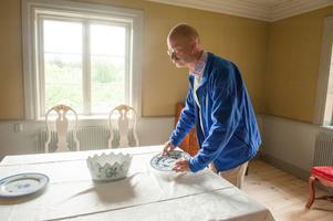 Mats- Einar Eriksson tittar på porslinet, som är kopior av Ostindiskt porslin från Rörstrand.
