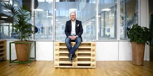 Dan Nilsson från Nykvarn, ny standardiseringschef på SIS, sätter sig glatt på en trave Europapallar, detta klassiska exempel på standardisering som revolutionerat både handel och transporter.