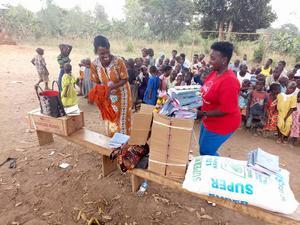 Volontärer på plats i Uganda delar ut skolmaterial till en grundskoleelever. Foto: Privat