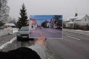 """En minibuss passerar på Stora vägen i Horndal en sommardag, något år efter högertrafikens införande 1967. Fotografen, Johannes Nielsen (1920-2007), var anställd i Horndals Jernverk och fick då och då i uppdrag att fotografera personal vid olika tillfällen. Många av porträtten hänger idag i bruksmuseet.""""Sjukvård"""" står det på huset till vänster. Det är färghandeln, som under de sista decennierna från 1955-99 ägdes av familjen Sjöberg. Gamla tiders färghandlare saluförde det mesta, däribland sjukvårdsprodukter.Längre bort på gatan signalerar en skylt platsen för samhällets ICA-butik. Den stora röda byggnaden till vänster bakom bussen bidrar till tidsbestämningen av fotot, eftersom det revs 1971. Det hade varit NTO-templet 269 Trygghets samlingsplats sedan 1901."""