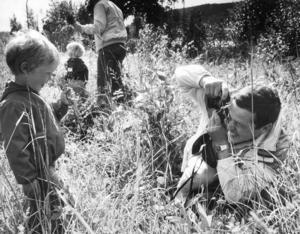 Midsommaren på Jamtli 1984 bjöd på glada barn och strålande väder. Här fotograferar pappan Lennart sin son Sam i grönskan. Foto: Sten Eklund.