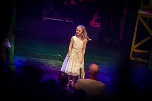 Tuvas andra stora roll på Storsjöteaterns scen är i Östersunsdrevyn. Här tackas hon med present i publiktacket på premiären på trettondagsafton.