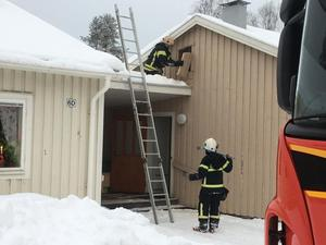 Arkivbild/En brandman sågar upp ett hål i ytterväggen för att kunna säkerställa så ingen eld eller rökutveckling pågår på vinden.