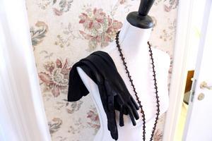 Långa pärlor och långa handskar mot tapeten med textil känsla.