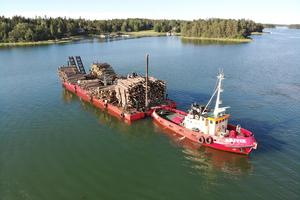 Timmer transporteras med hjälp av pråm till fastlandet, men än ligger många öar med vindfällen orörda. Foto: Henrik Ismarker/Spillersboda flygfoto