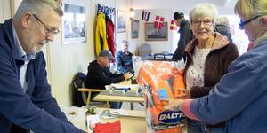 Håkan Björk packar ihop flaggspelet som Kristina Hedvall slog till på under båtloppisen i Kungsör. Hon funderade ett tag på att även köpa flytvästen av en annan försäljare men ångrade sig. Till vänster initiativtagaren Monica Eriksson.