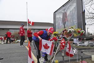 Sjuårige Jayden Duffy läser ett meddelande på en flagga som lämnats vid en minnesplats för Heidi Stevenson, en av de som dödades under jakten på en 51-årig massmördare.