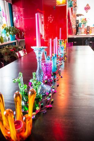 Färgglada ljusstakar av glas längs hela köksbordet.