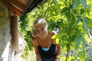 Berit tittar in under klematisen som klättrar på den gamla bykstugan som fått nytt tak.