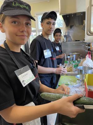 Indra, Khaled och Fidel förbereder i köket innan servering.  Foto: Margareta Englund