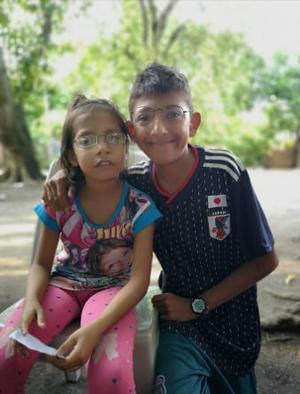 Ett syskonpar som fått fina glasögon utprovade. Glada och nöjda att de nu kan läsa läxorna. Foto: Privat