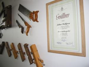 På väggen hänger en hel del gamla verktyg och ett bevis på att Johan Dahlgren kan det här med möbelsnickeri – ett gesällbrev. Att göra ett gesällprov är frivilligt, men är meriterande och visar att du behärskar hantverket.