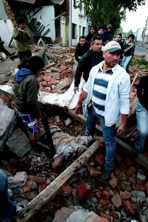 Boende i Talca står bredvid en död man som begravts i rasmassorna.