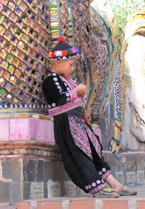 I en trappa upp till ett tempel i Thailand stod en liten kille fint uppklädd. Kanske någon turist vill knäppa ett kort på honom så att han kan tjäna en slant. Långtråkigt kan man tycka för en liten grabb med mycket spring i benen.