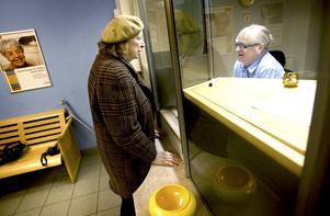 Kunden Gerd får hjälp av Christina Mårelius på Svensk Kassaservices kontor i Gävle. På lördag slår kontoret igen för gott som ett av de sista i Sverige. Gerd har varit anställd på Posten i 50 år och var en gång i tiden den som lärde upp Christina i jobbet.