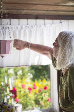 Monika rättar till den alldeles nyuppsatta gardinen på verandan.