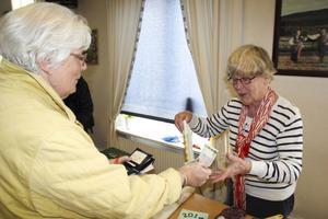 Berit Norin köper en stickad sittdyna av Husmodersföreningens kassör Janna André.