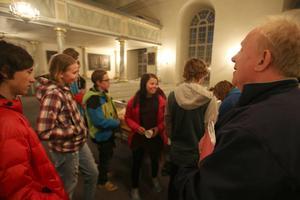 Församlingspedagog Per Rydberg hälsar ett gäng ungdomar välkomna in till kyrkan på Valborgskvällen.