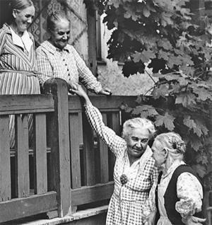 SOCIALT ENGAGEMANG. Sigrid Göransson (1872-1963), dotter till brukspatron Anders Henrik Göransson, här i samspråk med några kvinnor i Sandviken. Sigrid ansvarade för företagets sociala inrättningar, som blev ett föredöme när det gäller välfärdsåtgärder för de anställda.
