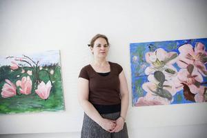 """MalinMatilda Allberg framför två av tavlorna i utställningen """"Växande"""". Tavlorna heter """"Första löftet om vår"""" och """"Körsbärsblom kantar sommarens entré""""."""