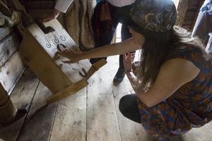 Caroline Pehrson får lära sig om gamla ting och vad inristningarna på baksidan står för. Denna stol användes när småbarn pottränades.
